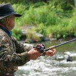fly fisherman casting in a river